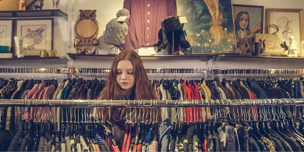 woman looking through clothing in a second hand store