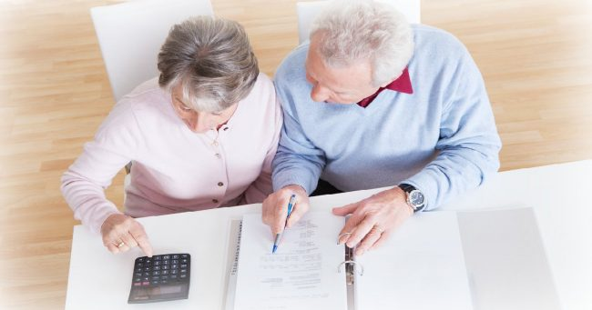 top view of an older couple looking over their finances in a binder and using a calculator