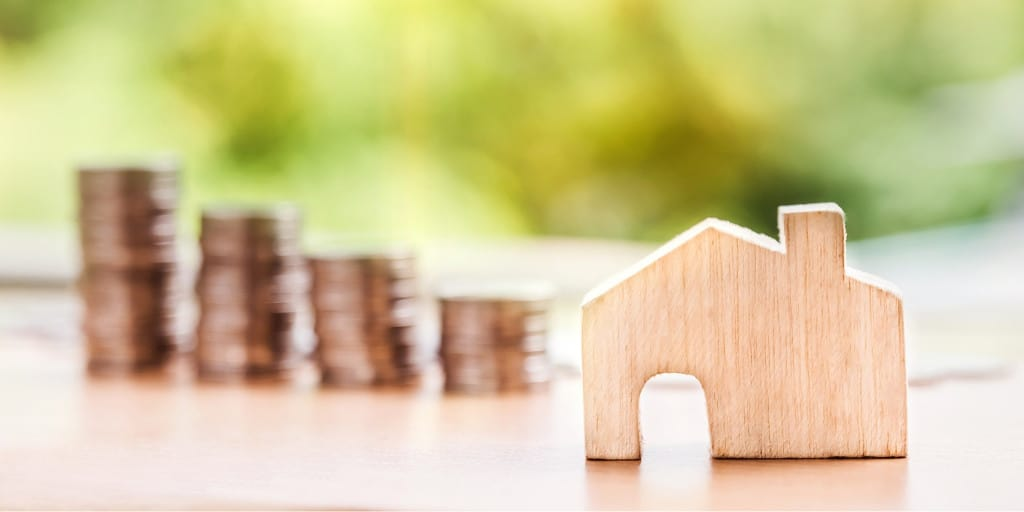 saving for first house depicted with stacks of coins and a model house