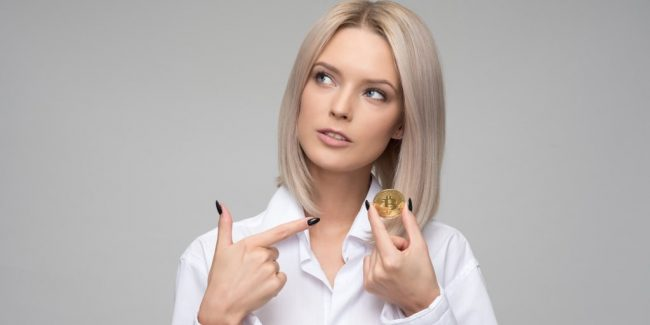 blonde female holding a coin representing a cryptocurrency