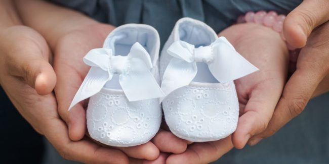 dainty white baby shoes held in hands of expectant parents