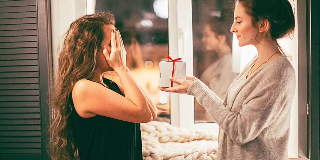 one woman surprising her friend with a gift