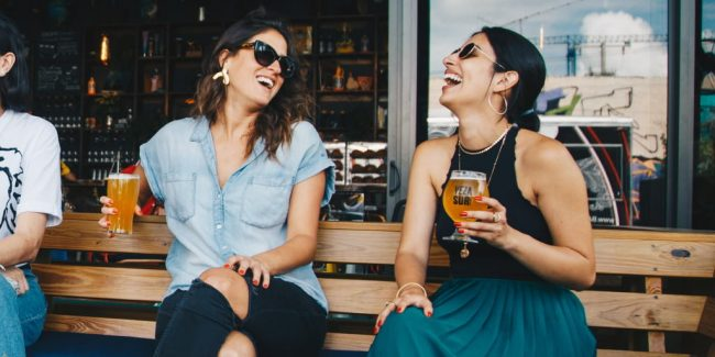 female friends enjoying a beer at an outdoor bar