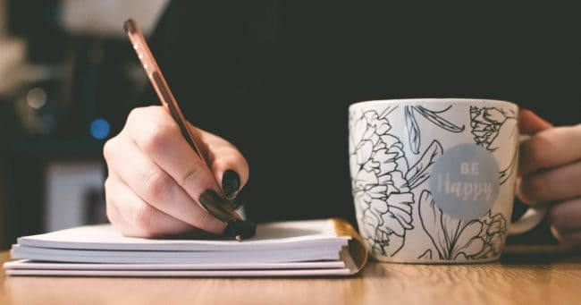 woman writing a financial mission statement