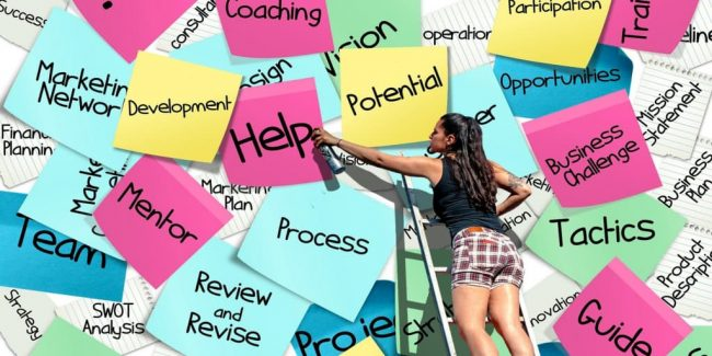 large post it notes with coaching words being painted on them