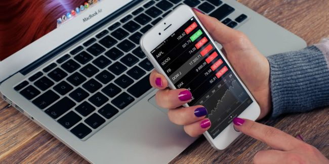 woman holding a smartphone looking at stock prices