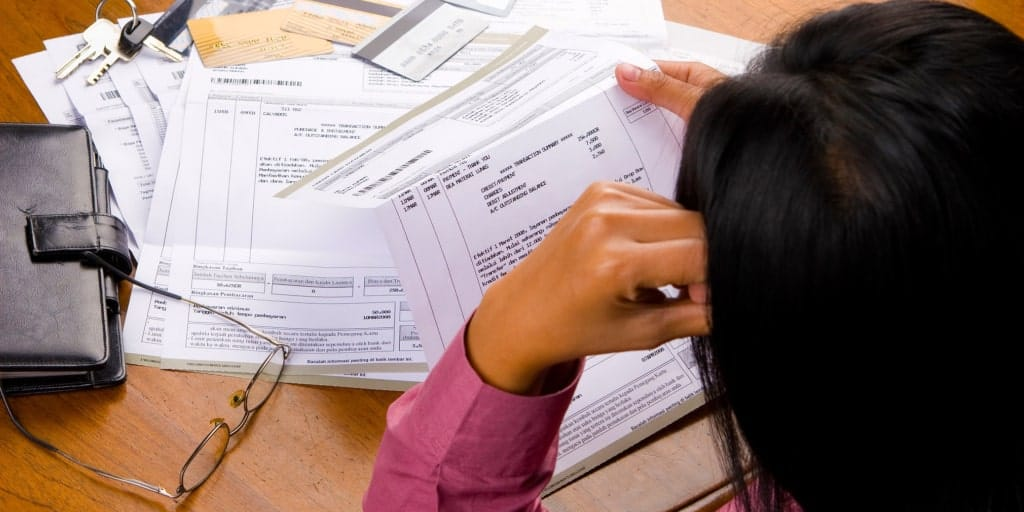 women looking at past due bills and debt collection letters