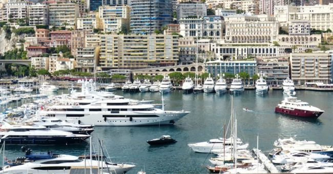 boats and yachts of the rich and wealthy docked in a bay near a big city
