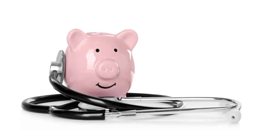 Pink piggy bank and stethoscope on white background