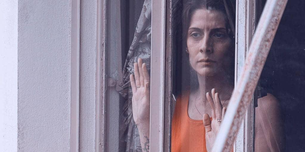 women looking fearful as she gazes out a window