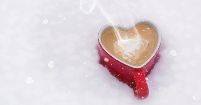heart shaped red mug full of hot chocolate sitting in snow