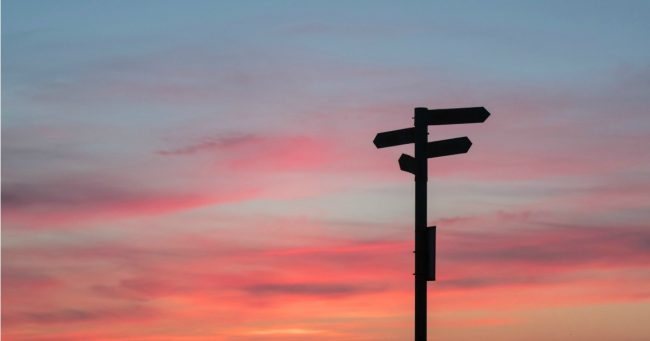 directional sign silhouette agains gorgeous sunset