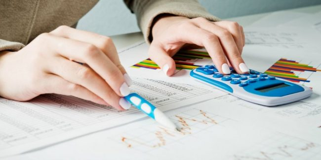 female calculating losses and gains from stock market to see if tax loss harvesting will work for her