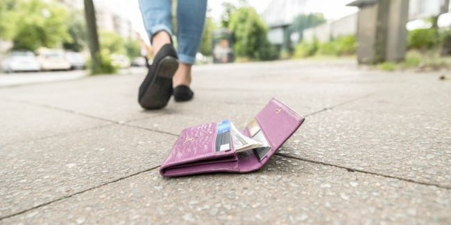 lost womens wallet laying open on a sidewalk