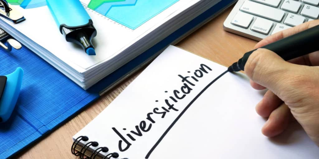person writing the word diversification in notebook with black felt marker