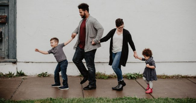 two parents and two children walking on sidewalk
