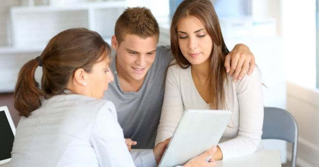 young couple speaking with a financial advisor