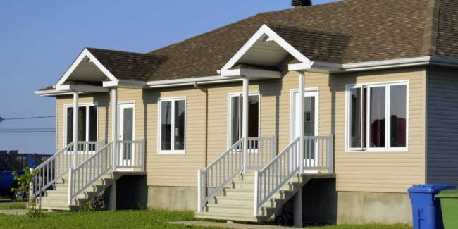 duplex home with tan siding, white trim, and a brown roof