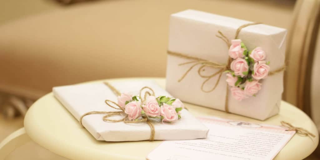 two wrapped wedding gifts on small round table