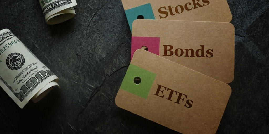 etf bonds and stock tags on table with rolls of money