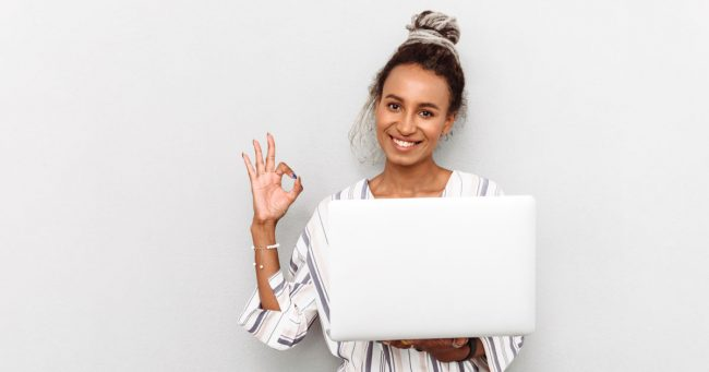 female entrepreneur holding laptop and giving okay sign