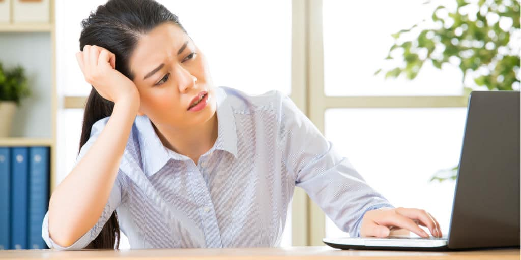 Young asian business woman unhappy working in office