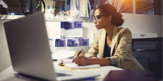 young black women working on her professional development at a desk in her office