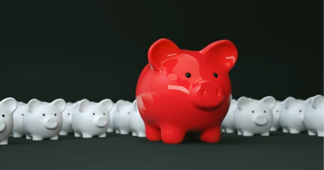 red piggy bank amongst sea of white piggy banks