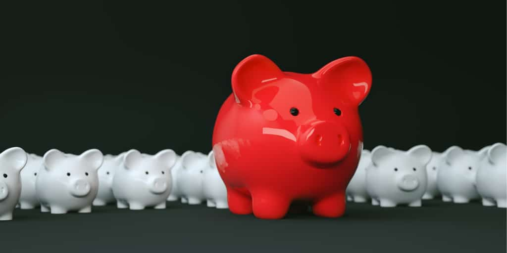 red piggy bank in front of many white piggy banks symbolizing an accredited investor