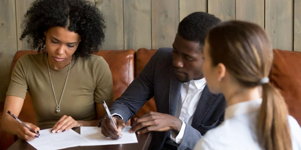 black couple signing a purchase offer for a house