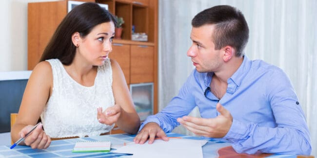 Family couple with money problems making shopping list indoors