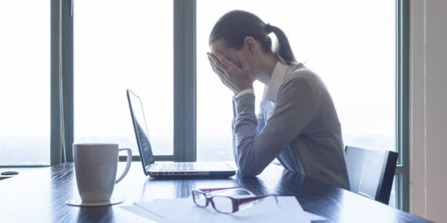 cpa in her office stressed over her massive debt