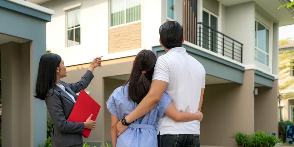 real estate agent showing housing to a couple