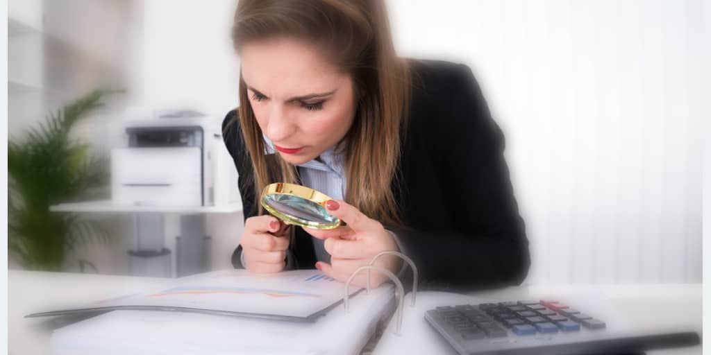 woman reviewing financial tax documents with a magnifying glass