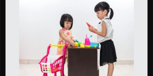 Asian Chinese little sisters pretending as customer and cashier with toy shopping cart and cash register