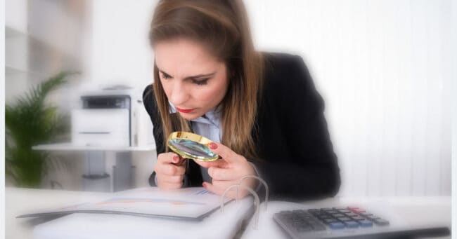 woman reviewing financial and tax documents in a binder with a magnifying glass, calculator on desk beside her
