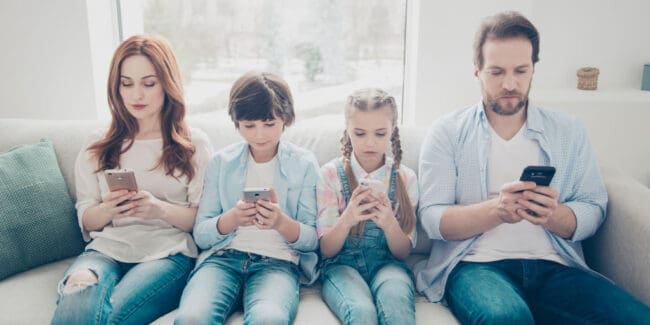 two parents and two kids sitting on couch and looking at their smart phone money apps