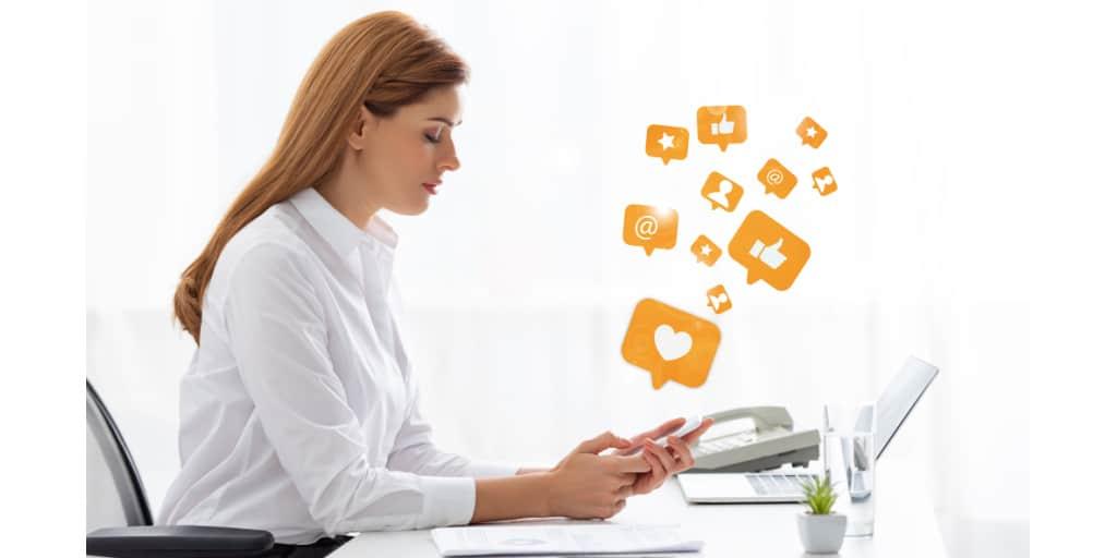 female social media manager on smartphone at her desk
