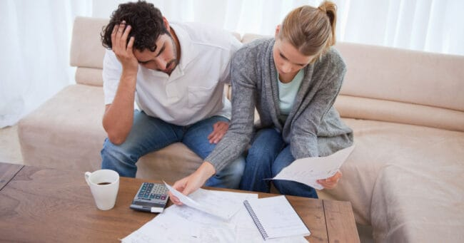 Depressed couple going over their debt in their living room