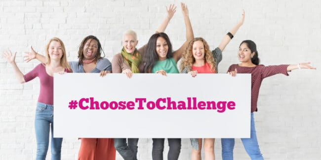 group of women holding a sign that reads choose to challenge and raising arms in celebration