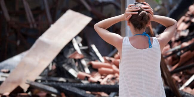 Woman standing in front of burned out house with both hands on her head