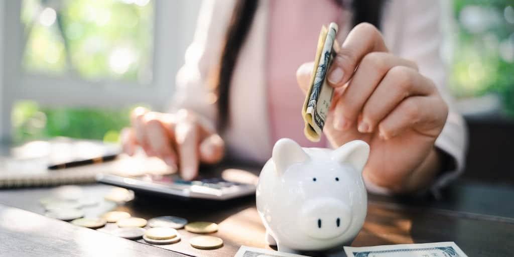 Closeup of woman hand putting money into piggy bank for saving money. saving money and budgeting concept