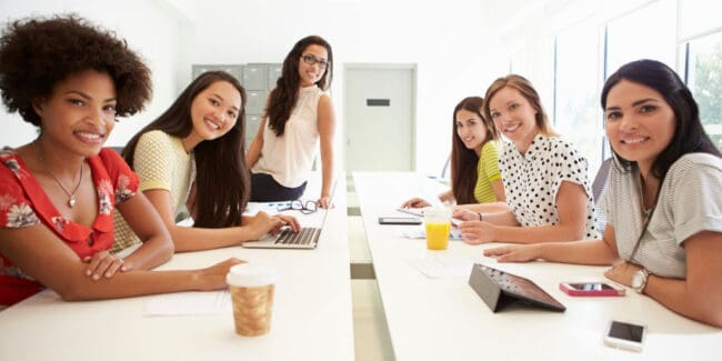 new female college graduates at work in a company conference room