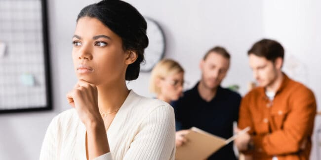 pensive african american in the workplace with group of other employees conversing behind her
