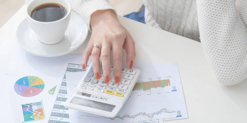 woman using a calculator and financial documents to create a financial plan