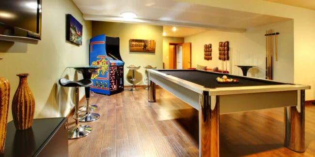 finished basement entertainment area with pool table and pinball machine