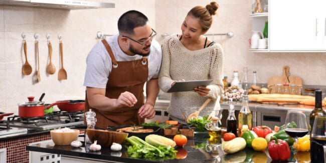 Loving young Asian couple using digital tablet and meal prepping in kitchen making healthy food together feeling fun