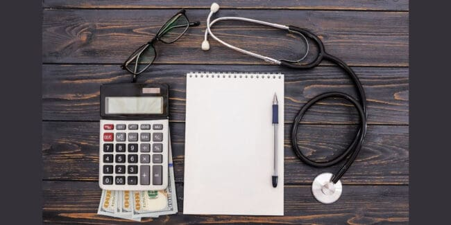 calculator, cash, stethoscope, and notepad on desktop symbolizing saving money for healthcare in a medical savings account