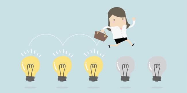 woman carrying briefcase jumping on light bulbs symbolizing job hopping