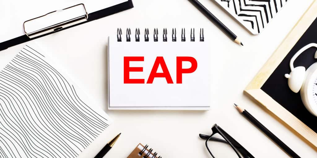 red letters E A P on note card in center of work desk
